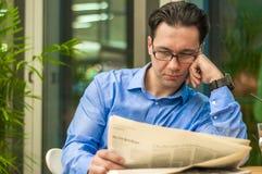 Retrato de um homem de negócios considerável novo que lê um jornal em seu café da manhã na cafetaria Fotografia de Stock