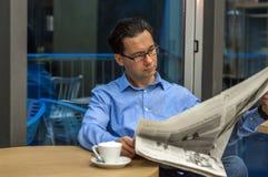Retrato de um homem de negócios considerável novo que lê um jornal em seu café da manhã na cafetaria Imagens de Stock Royalty Free