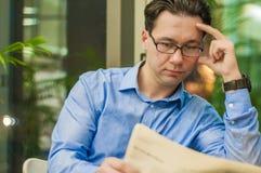 Retrato de um homem de negócios considerável novo que lê um jornal em seu café da manhã na cafetaria Foto de Stock Royalty Free