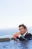 Retrato de um homem de negócios de sorriso que relaxa em uma piscina   Imagens de Stock
