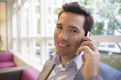 Retrato de um homem de negócios novo de sorriso que usa o telefone celular no sofá, foto de stock