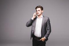 Retrato de um homem de negócios que fala no telefone celular isolado em um fundo cinzento Imagens de Stock Royalty Free