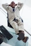 Retrato de um homem de negócios de sorriso que relaxa Imagem de Stock Royalty Free