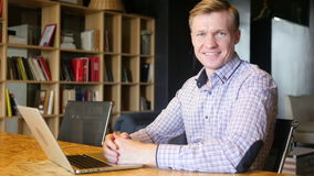 Retrato de um homem de sorriso profissional novo elegante em um escritório, sorrindo vídeos de arquivo