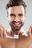 Retrato de um homem de sorriso que põe o dentífrico sobre uma escova de dentes Imagens de Stock