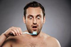 Retrato de um homem descamisado chocado que guarda a escova de dentes foto de stock royalty free