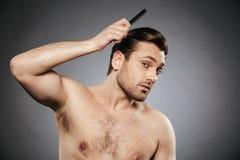Retrato de um homem descamisado concentrado que penteia seu cabelo foto de stock