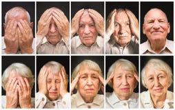 Retrato de um homem e de uma mulher idosos com a cara fechado pelas mãos foto de stock