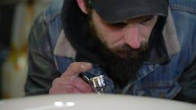 Retrato de um homem farpado adulto em um tampão com as tatuagens que tiram com o aerógrafo na oficina vídeos de arquivo