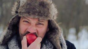 Retrato de um homem farpado com uma maçã no inverno Um homem farpado novo come uma maçã no inverno vídeos de arquivo