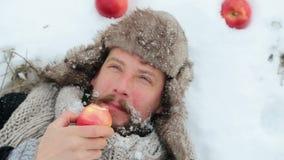 Retrato de um homem farpado com uma maçã no inverno Um homem farpado novo come uma maçã no inverno filme