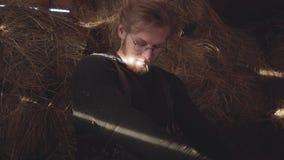 Retrato de um homem farpado considerável com os vidros que sentam-se em um feno em um estábulo O indivíduo agita o feno de sua ca video estoque