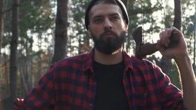 Retrato de um homem farpado em uma camisa de manta que está com um machado em sua mão na floresta Indivíduo sério brutal com mach vídeos de arquivo