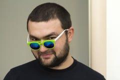 Retrato de um homem farpado novo considerável em vidros verdes Fotografia de Stock