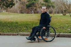 Retrato de um homem feliz em uma cadeira de rodas em um parque fotografia de stock royalty free