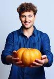 Retrato de um homem feliz que guarda a abóbora Imagem de Stock Royalty Free