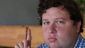 Retrato de um homem gordo novo que tem a ideia e que aponta o dedo acima no café ou no restaurante vídeos de arquivo