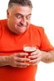 Retrato de um homem gordo sedento que olha fixamente em um vidro da cerveja Fotos de Stock Royalty Free
