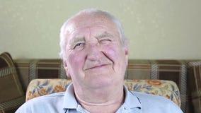 Retrato de um homem idoso Olhando a câmera e as piscadelas vídeos de arquivo