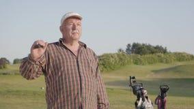 Retrato de um homem maduro bem sucedido seguro com um clube de golfe que está em um campo de golfe no bom tempo ensolarado esport video estoque
