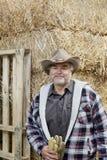 Retrato de um homem maduro feliz com o chapéu de vaqueiro que guarda luvas na frente da pilha do feno Fotografia de Stock Royalty Free