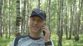 Retrato de um homem de meia idade feliz Vai dentro para esportes no parque e fala no telefone Um dia ensolarado bonito vídeos de arquivo