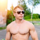 Retrato de um homem moderno considerável, um halterofilista do indivíduo do atleta na natureza, escutando nos fones de ouvido a m Fotos de Stock Royalty Free