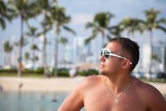 Retrato de um homem muscular 'sexy' molhado novo que está na praia Foto de Stock
