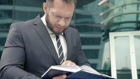 Retrato de um homem de negócio ansioso que tenta encontrar algo em um caderno vídeos de arquivo
