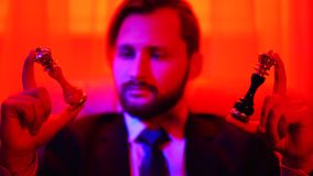 Retrato de um homem de negócios bem sucedido em um terno de negócio que guarda uma figura branca e preta da xadrez em seus braços filme