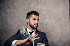 Retrato de um homem de negócios considerável novo que joga para fora cédulas do dinheiro terno vestindo e um laço imagens de stock