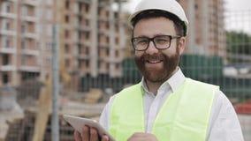 Retrato de um homem de negócios novo bem sucedido, vestindo um capacete branco, em um terno que trabalha com a tabuleta que olha  filme