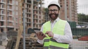 Retrato de um homem de negócios novo bem sucedido, vestindo um capacete branco, em um terno que trabalha com a tabuleta que olha  vídeos de arquivo