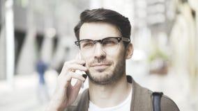 Retrato de um homem de negócios que fala seu telefone esperto na rua e que olha a câmera Foto de Stock