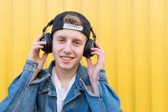 Retrato de um homem novo à moda que escute a música em fones de ouvido sem fio no fundo de uma parede amarela fotografia de stock