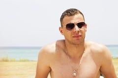 Retrato de um homem novo atrativo em uma praia imagem de stock