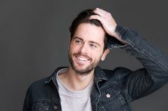 Retrato de um homem novo atrativo que sorri com mão no cabelo Foto de Stock