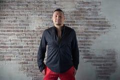 Retrato de um homem novo, carnudo, vestido em folgas vermelhas e em uma camisa preta imagem de stock royalty free