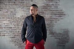 Retrato de um homem novo, carnudo, vestido em folgas vermelhas e em uma camisa preta Fotos de Stock