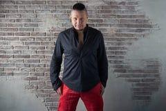 Retrato de um homem novo, carnudo, vestido em folgas vermelhas e em uma camisa preta imagem de stock