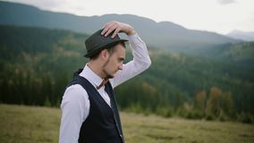 Retrato de um homem novo cercado por natureza Homem que desgasta um chapéu Movimento lento filme