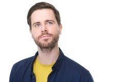 Retrato de um homem novo com a barba que olha acima e que pensa Imagens de Stock Royalty Free