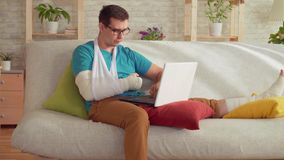 Retrato de um homem novo com um braço e um pé quebrados que sentam-se no sofá e nos usos um portátil filme