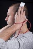 Retrato de um homem novo com os fones de ouvido em sua cabeça no perfil Imagem de Stock Royalty Free