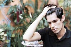 Retrato de um homem novo com sua mão em seu cabelo, pensando foto de stock royalty free