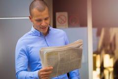 Retrato de um homem novo considerável ao ler o jornal imagem de stock
