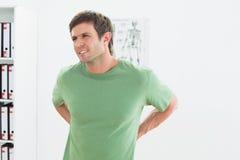 Retrato de um homem novo considerável com dor nas costas Fotografia de Stock