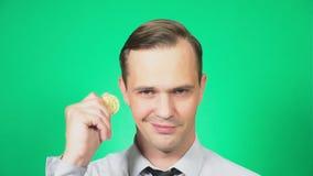Retrato de um homem novo considerável que guarda um bitcoin da moeda em sua mão Olha a moeda e os lances ele Foco no video estoque
