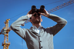 Retrato de um homem novo considerável que olha através dos binóculos Imagem de Stock
