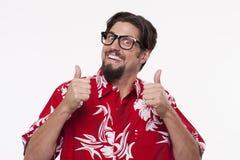 Retrato de um homem novo de sorriso que mostra os polegares acima contra o branco Imagens de Stock